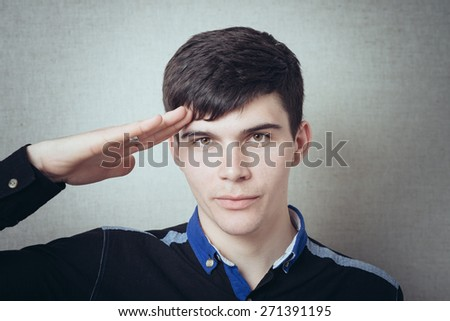 man salutes his hand to his temple - stock photo