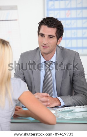 Man sat at desk talking to blond female
