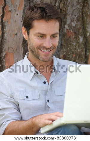 Man sat by tree with laptop computer - stock photo