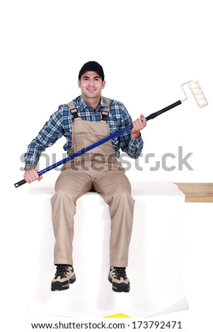Man sat with paint roller - stock photo