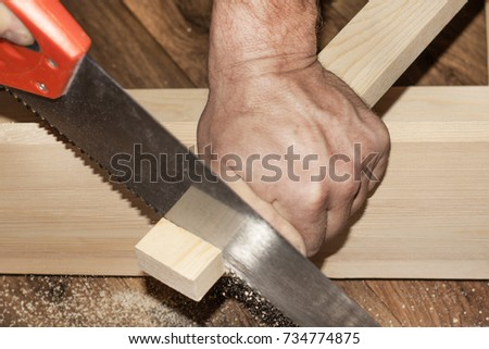 Man sawing wood Board with hand saw