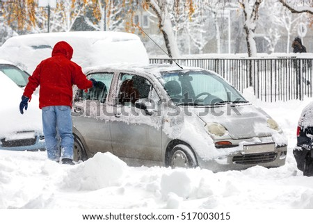 Man scraping frozen snow from the car windows during the heavy snowfall