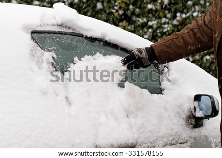 Man scraping snow and ice from car window - stock photo