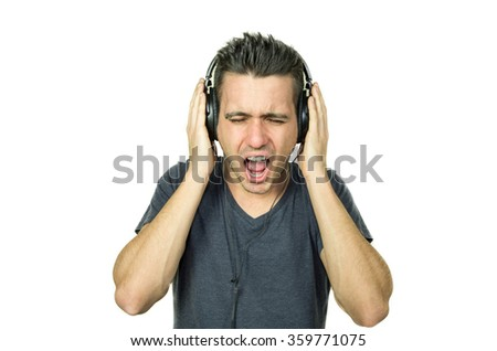 Man scream while listening music with his headphones - people and technology concept - caucasian people - stock photo
