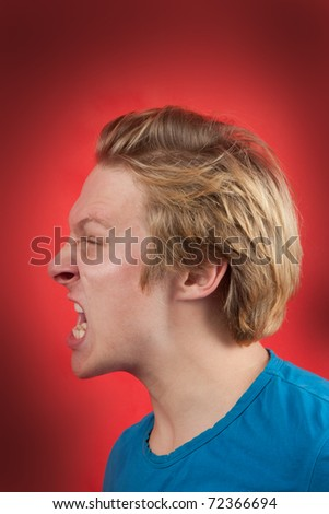 Man screaming in profile view with red background - stock photo