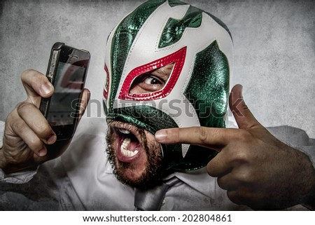 man screaming on the phone, aggressive executive suit and tie, Mexican wrestler mask - stock photo