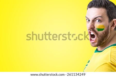 Man screaming on yellow background - stock photo