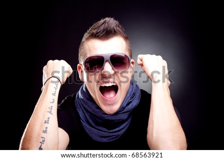 man screaming with fists in the air - studio shot - stock photo