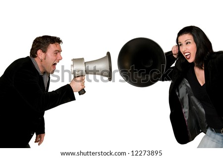 Man screaming with megaphone at woman listening with huge hearing aid - stock photo
