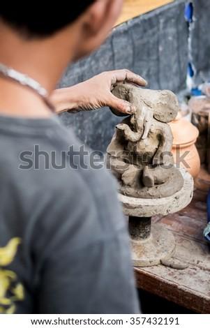 Man sculpt elephant from clay. - stock photo
