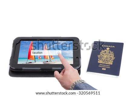 Man searching vacation destination a tablet with Canadian passport on white background - stock photo