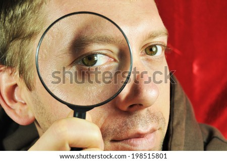 Man searching with magnifying glass - stock photo