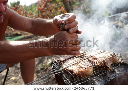 Man seasoning pork chops with pepper at the picnic - stock photo