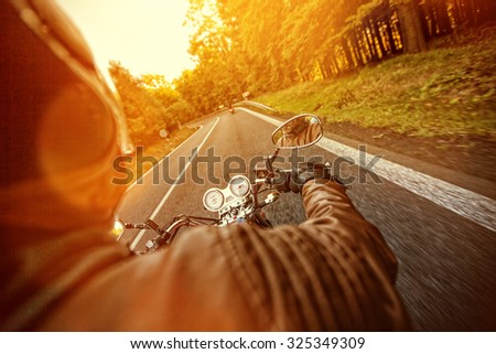 Man seat on the motorcycle on the forest road. - stock photo