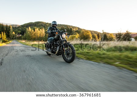 Man seat on the motorcycle on the forest road during sunrise. - stock photo
