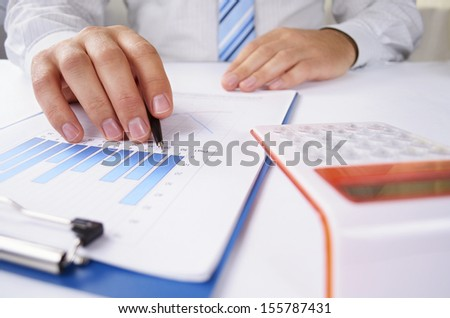 Man seated at his desk working on analysing a bar graph holding a pen and using a calculator, close up low angle view of his hands
