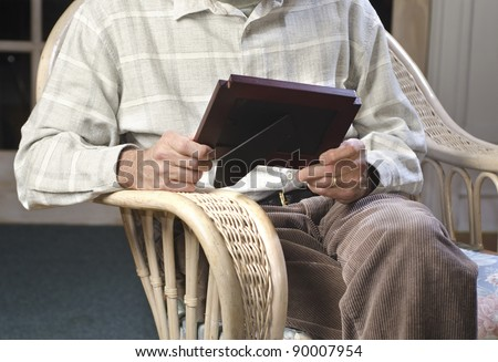 man seated on easy chair looking at picture frame
