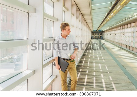 Man seeking love in New York. Wearing white shirt, yellow pants, carrying laptop computer, holding white rose. a young guy standing on walk way on campus, waiting for you. Instagram effect.  - stock photo