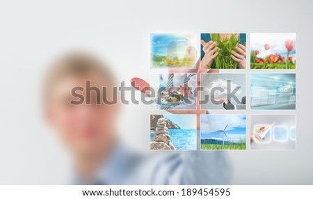 Man selecting tv channel on virtual touch screen - stock photo