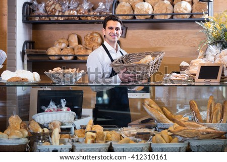 Man selling fresh  bread and baguettes in local bakery - stock photo