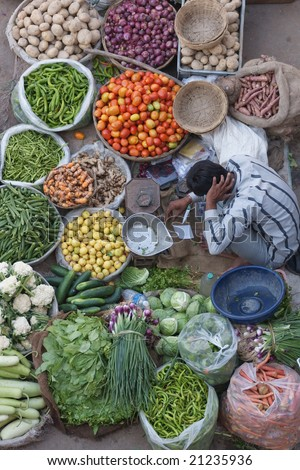 Man selling fruit and veg at a street market in Pushkar, Rajasthan, India - stock photo