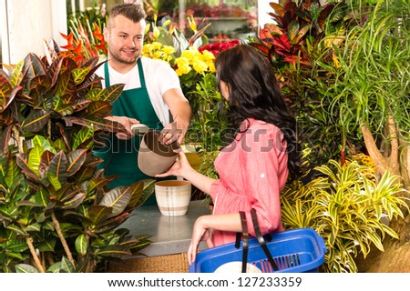 Man selling pot woman customer flower shop gardening plant - stock photo