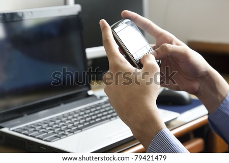 man sending or reading sms on his mobile phone