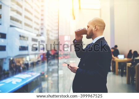 Man serious entrepreneur is drinking take away coffee, while is standing with mobile phone in hand in co-working cafe. Skilled businessman is watching in window and thinking about his future meeting - stock photo