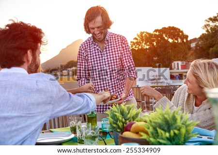 Man serves friends skewer kebabs at outdoor rooftop barbeque dinner party - stock photo