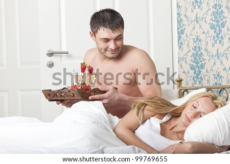 man serving breakfast to bed with two glasses sparkling wine - stock photo