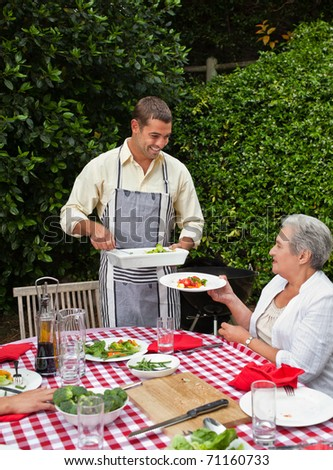 Man serving his family at the table - stock photo