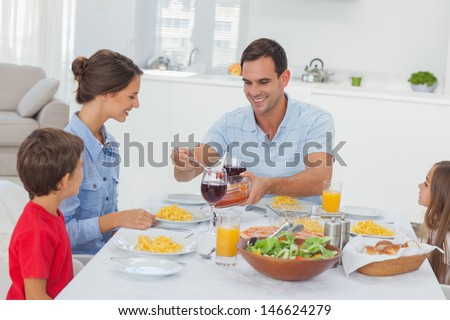 Man serving wife during the family dinner  - stock photo