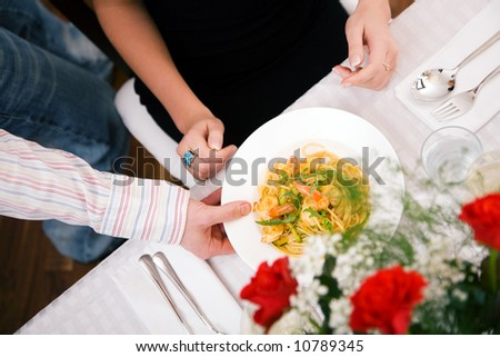 Man serving woman a plate of pasta, domestic setting (selective focus on the food) - stock photo