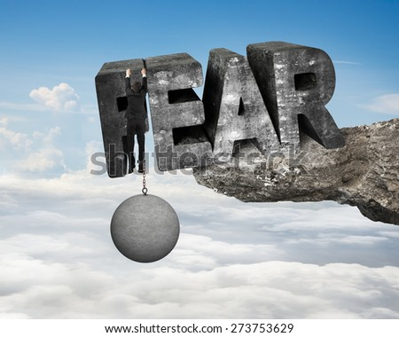Man shackled by heavy concrete ball hanging on big 3D fear mottled word at the edge of cliff with blue sky clouds background - stock photo