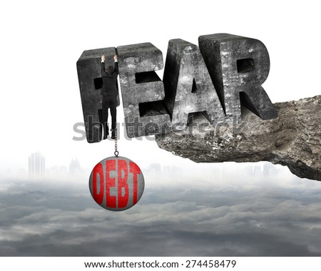 Man shackled by heavy red debt ball hanging on big 3D fear mottled concrete word at the edge of cliff with white background - stock photo