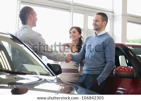 Man shaking a car dealer hand with his wife - stock photo