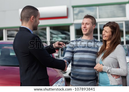 Man shaking hand with salesman in a dealership - stock photo