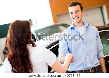 man shaking hands with car salesman, buying a new car - stock photo