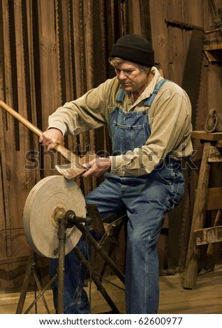 man sharpening an axe on an old pedal powered grinding stone - stock photo