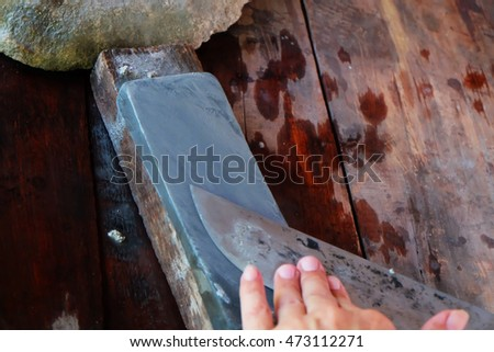 Man sharpening the knife with whetstone