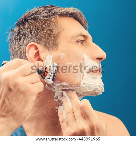 Man shaves. Side view - stock photo