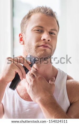 Man shaving. Handsome young man shaving with electric razor - stock photo