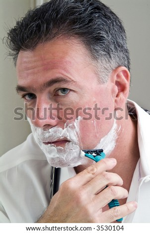Man shaving trying to get ready for work. - stock photo