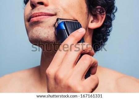 Man shaving with electric razor - stock photo
