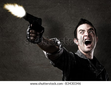 man shooting a gun against a eroded wall