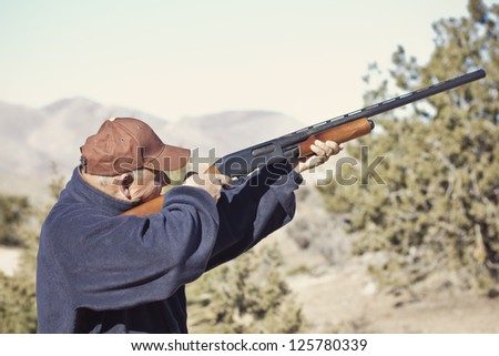 Man Shooting a Shotgun Hunting - stock photo