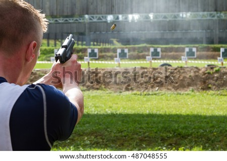 Man shooting at a green target on an outdoor shooting range, focus on gun