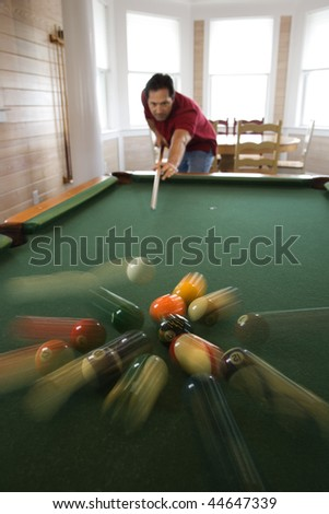 Man shooting game of pool with balls scattering after hit. - stock photo