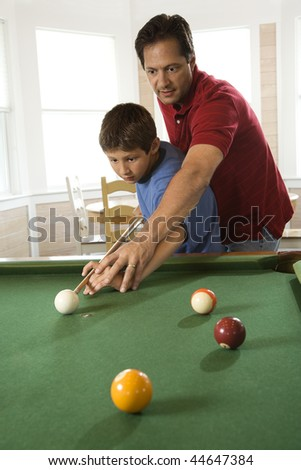 Man shooting game of pool with young boy.  Vertically framed shot. - stock photo