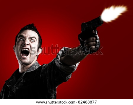 man shooting on a red background - stock photo